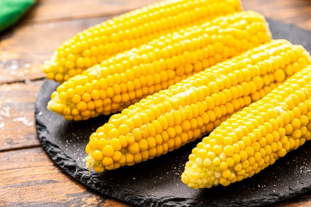 Four pieces of corn on the cob on a slate round board.