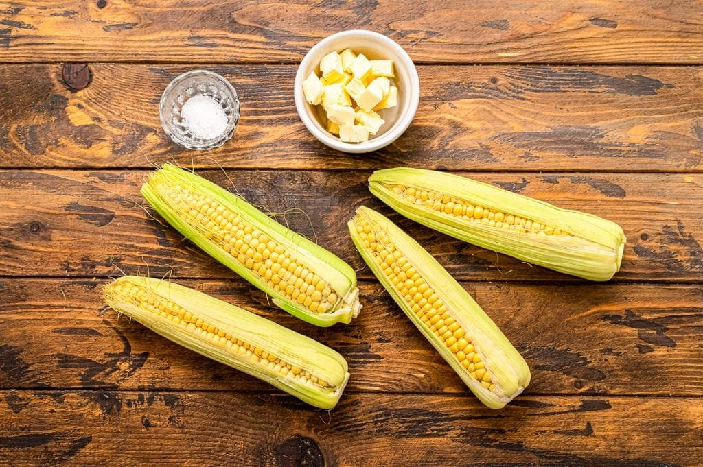 Overhead image of corn on the cob, salt and butter.