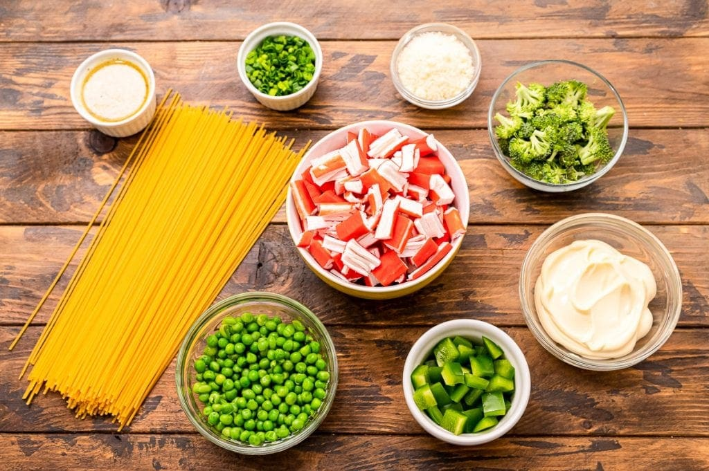 Overhead image showing ingredients for salad like spaghetti noodles, green onions, peas, broccoli, mayonnaise, etc.