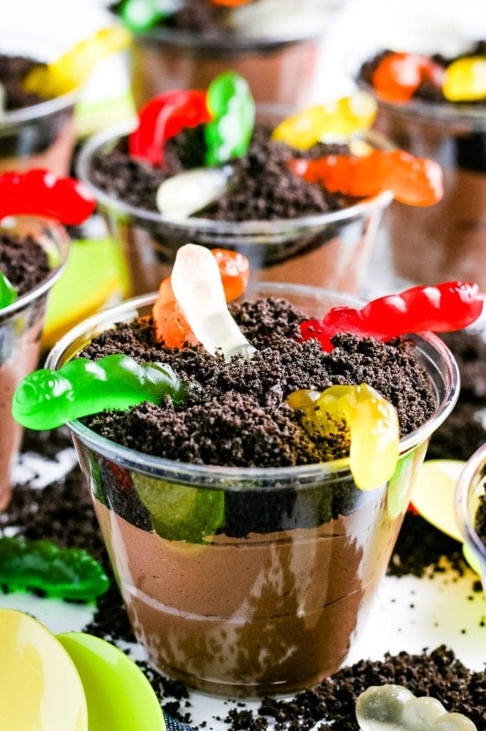 Close up of a Oreo Dirt Cup with gummy worms with more in the background.