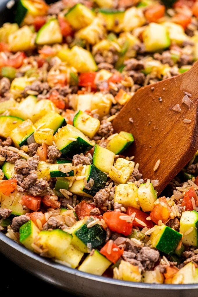 Wooden Spoon stirring ground beef and zucchini mixture.