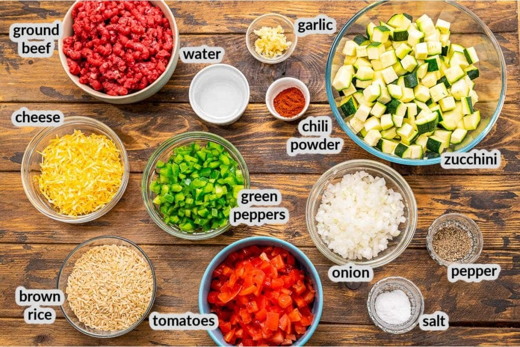 Overhead image showing ingredients in bowls for hamburger and zucchini skillet on wooden background