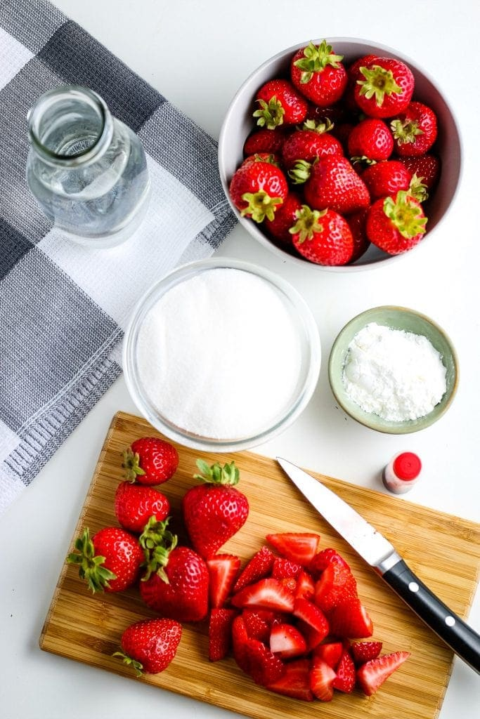Wood cutting board with chopped strawberries on it along with the rest of the ingredients in background for strawberry sauce.