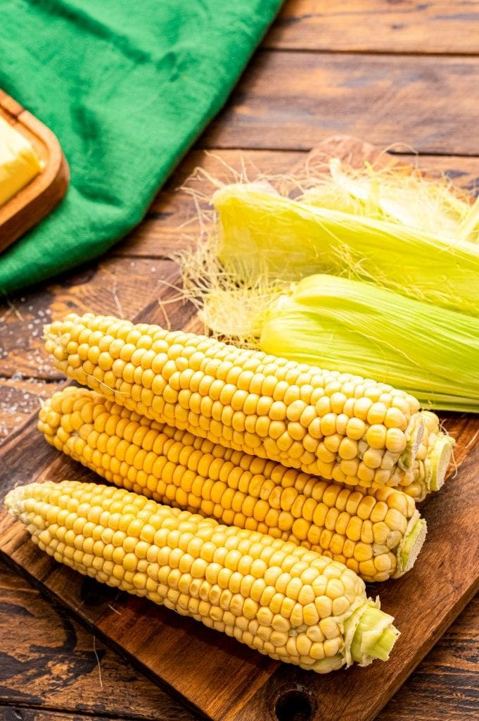 Four pieces of corn on the cob on a wood cutting board with husk behind them.