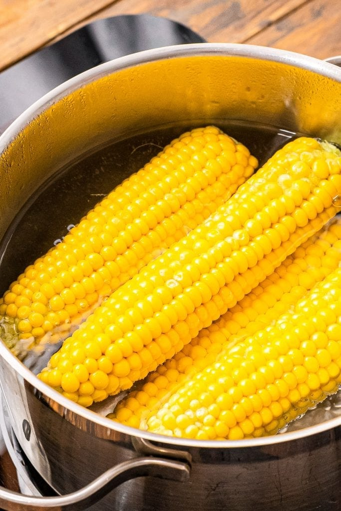 A pot with corn on the cob and water in it.