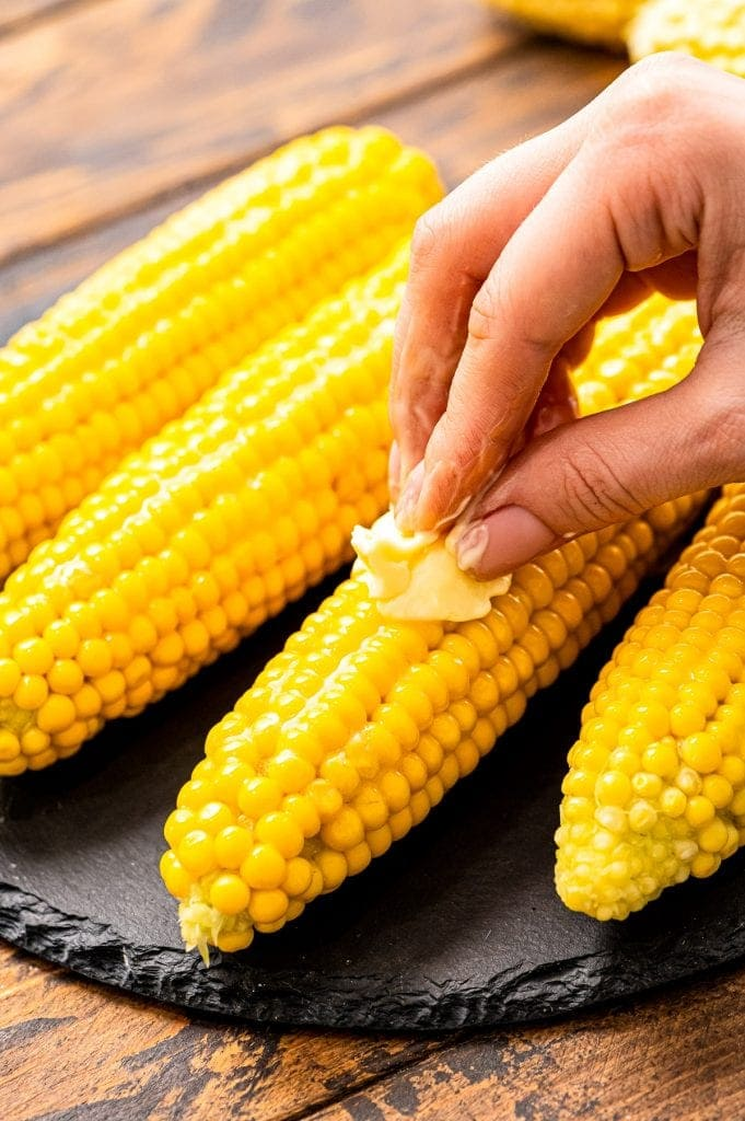 Hand rubbing a slice of butter over a piece of corn on the cob.