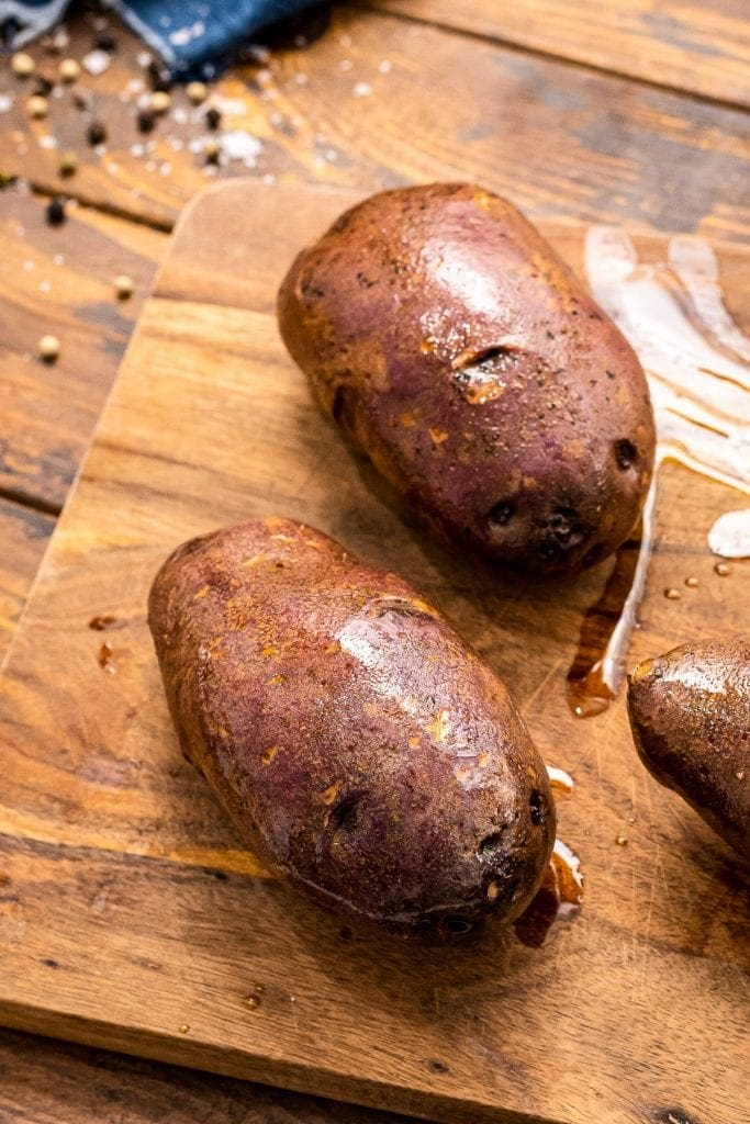 Potatoes coated in oil on a wooden in cutting board