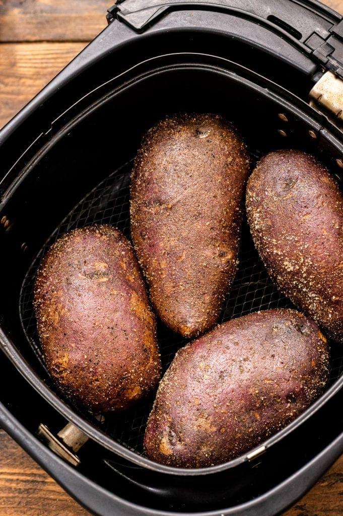 Air Fryer basket with seasoned potatoes in it