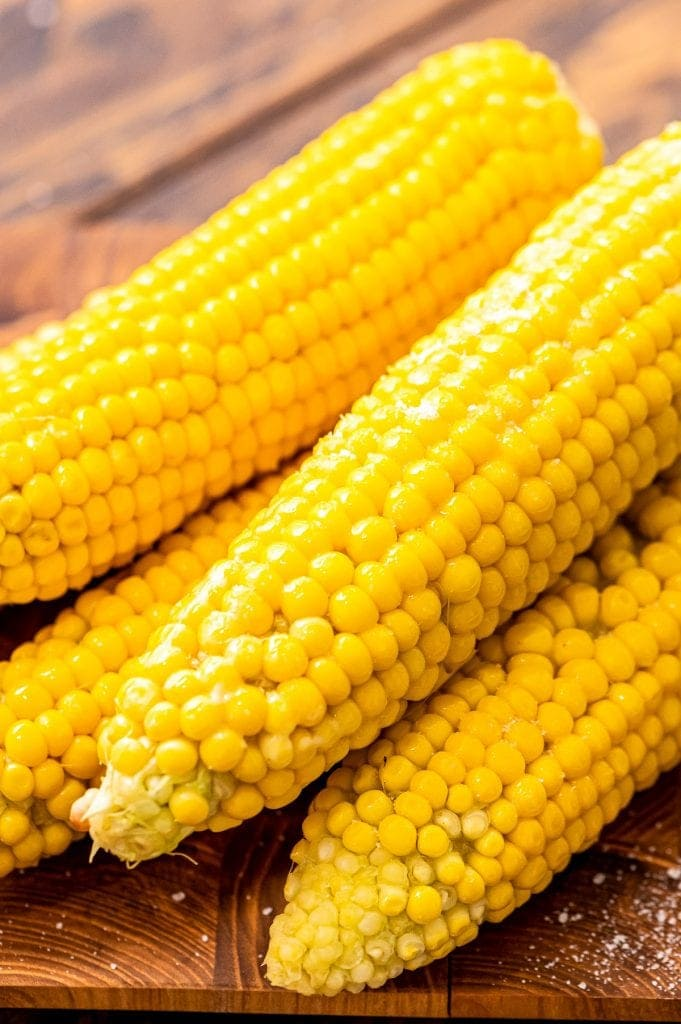 Portrait image showing cooked corn on the cob that is slightly stacked.