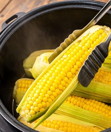 Tongs lifting a piece of corn on the cob with husk on out of Instant Pot.