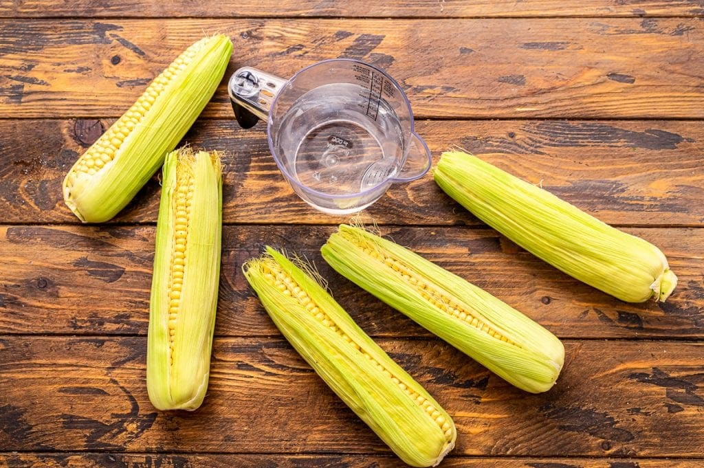 Overhead image of corn on the cob in husks and a cup of water.