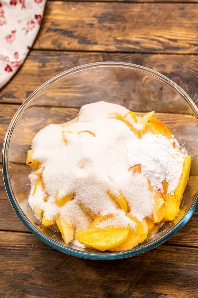 Glass bowl with fresh sliced peaches on bottom and sprinkled with sugar and tapioca.