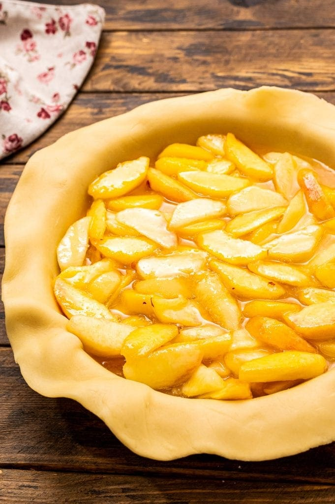 Pie Crust in pie dish filled with peach pie filling.