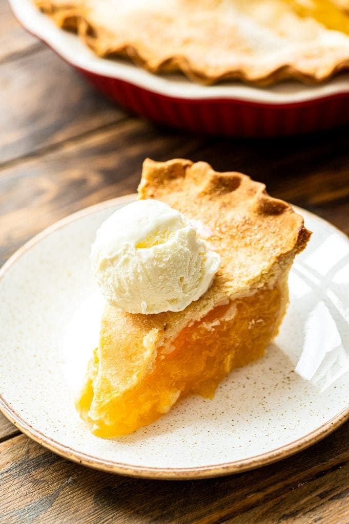Slice of peach pie topped with ice cream on a light colored plate. Full peach pie in background