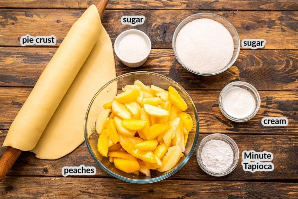 Overhead image of ingredients for peach pie including crust, peaches, sugar, cream, tapioca.