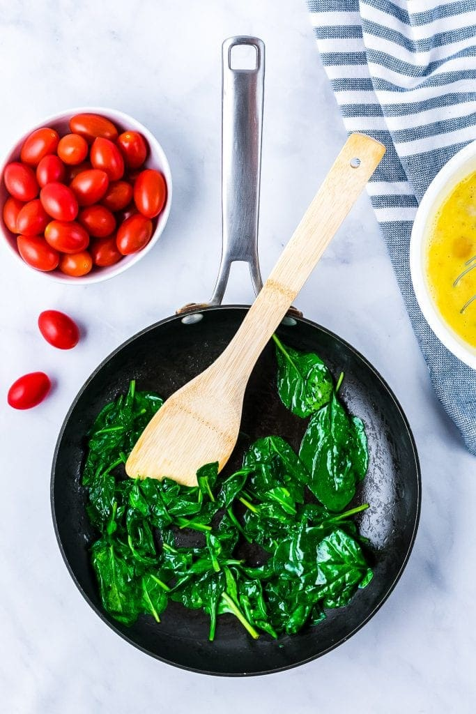 Cast Iron skillet with wilted spinach, a bowl of cherry tomatoes on light background