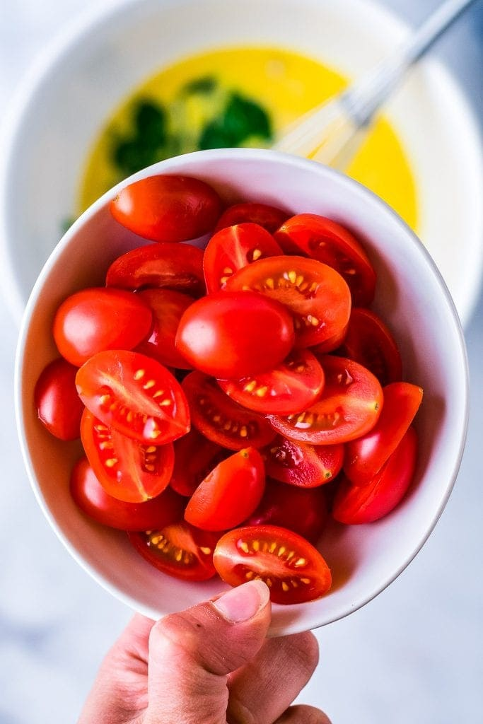 Hand holding white bowl with halved tomatoes