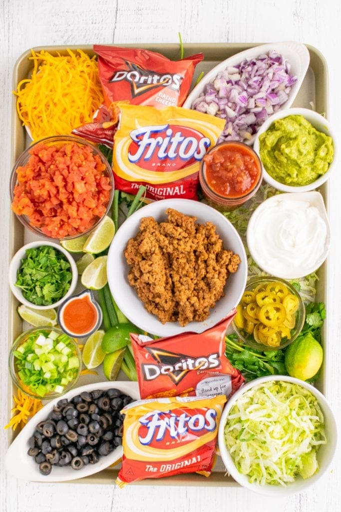 Overhead photo of sheet pan with bowls of taco toppings in bowl along with tomato, green onion to garnish. Small bowls of salsa and guacamole added plus small bags of Fritos and Nacho Cheese Doritos.