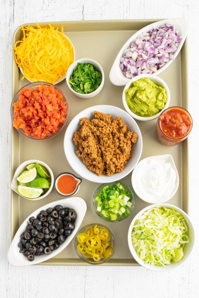 Overhead photo of sheet pan with bowls of taco toppings