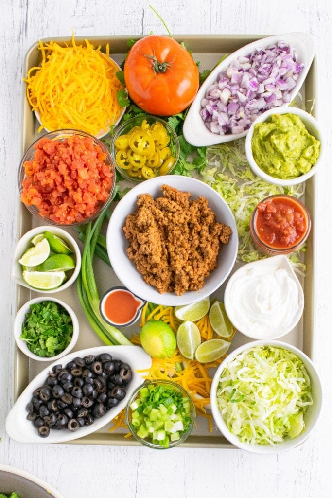 Overhead photo of sheet pan with bowls of taco toppings in bowl along with tomato, green onion to garnish. Small bowls of salsa and guacamole added.