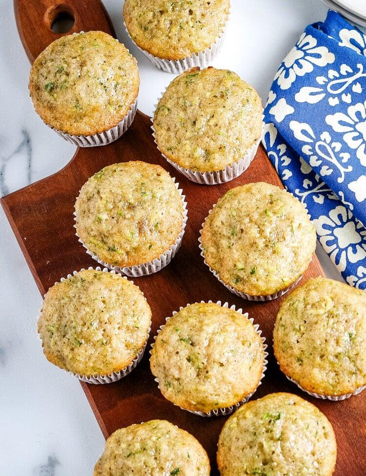 Overhead image of zucchini muffins on wood cutting board.