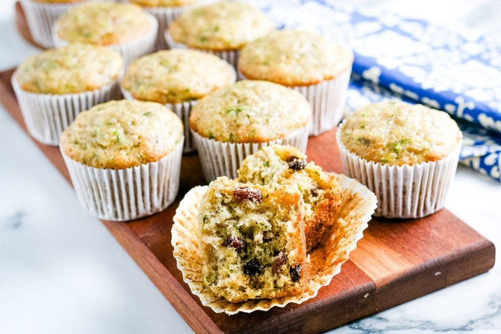 Zucchini muffin cut in half on muffin liner with more muffins behind it.