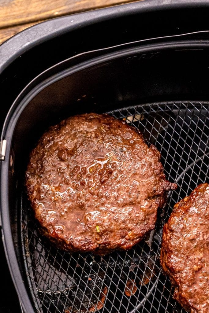 Cooked burgers in air fryer basket