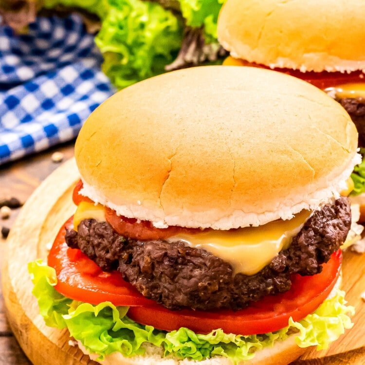 Wood platter with a burger in a bun topped with cheese, lettuce and tomato