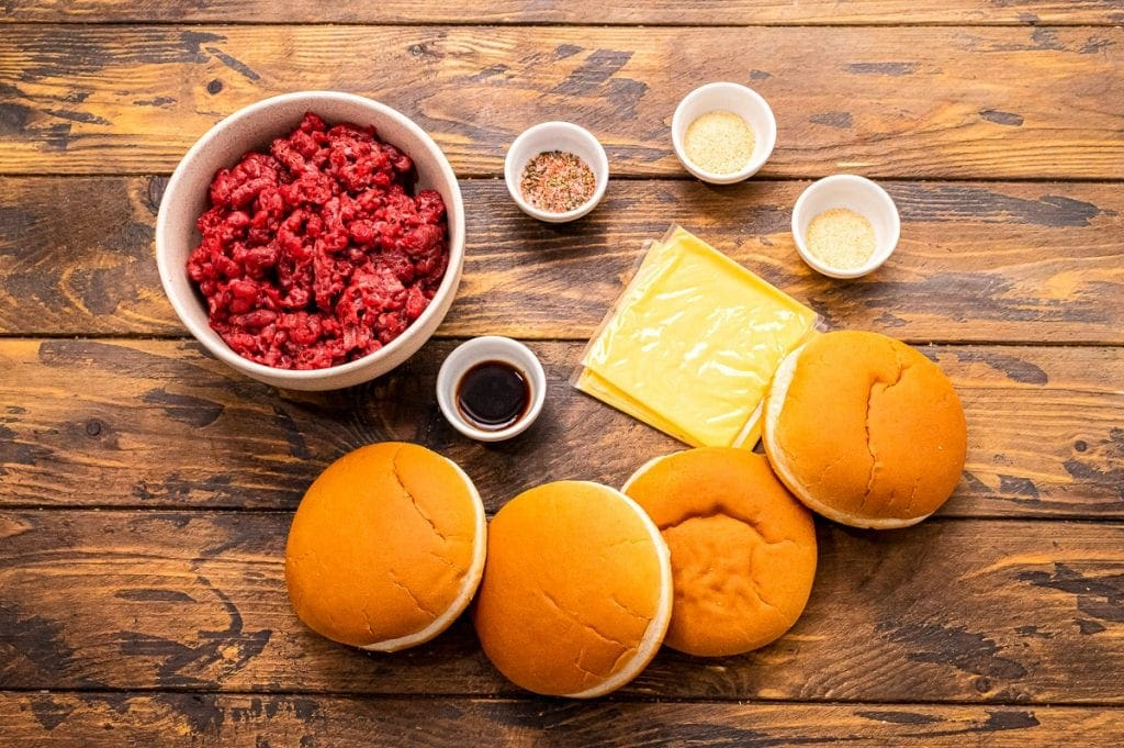 Wood background with ingredeints for hamburgers in small bowls like ground beef, buns, cheese slices and seasonings