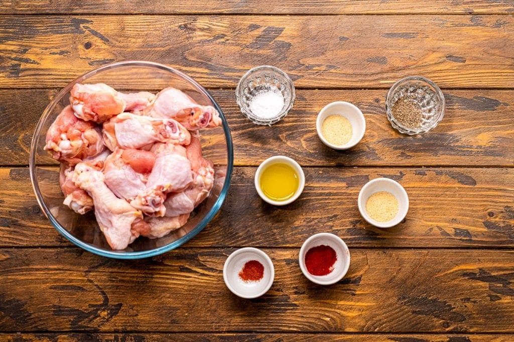 Overhead image of ingredients including a bowl of chicken wings, seasonings in multiple bowls and olive oil in a bowl