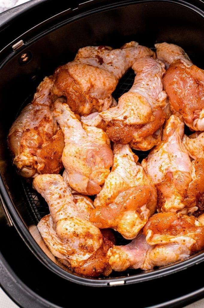 Air fryer basket with seasoned chicken wings.
