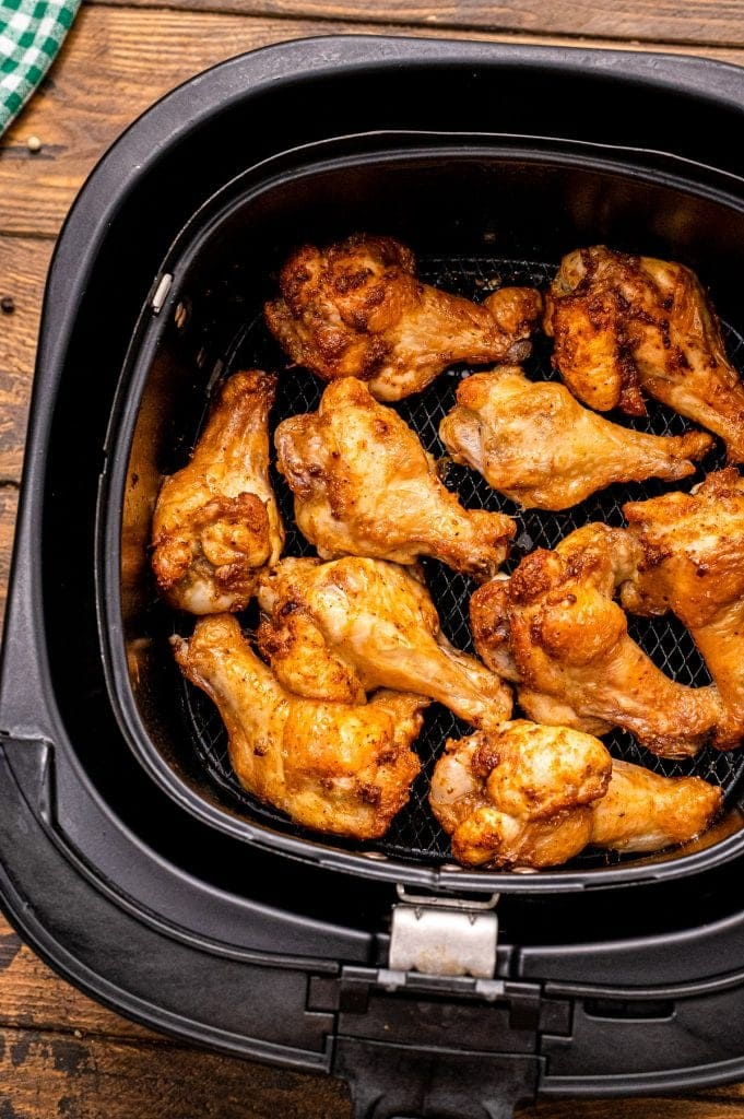 Air Fryer basket with cooked chicken wings in it.