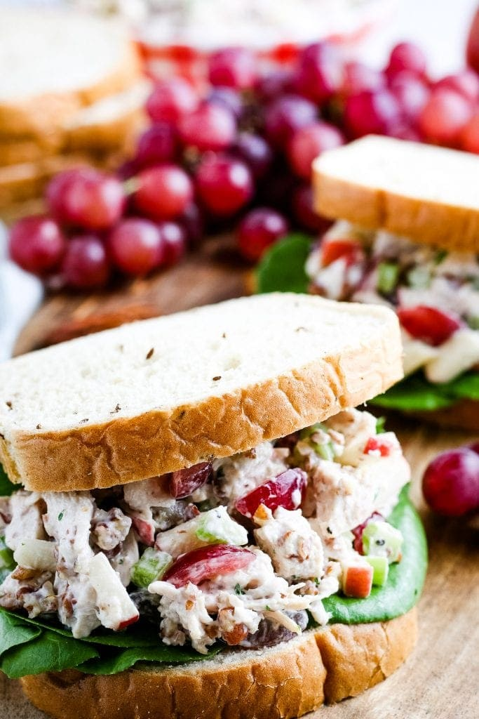 Close up image of sandwich filled with chicken salad and lettuce. Grapes and another sandwich in background.