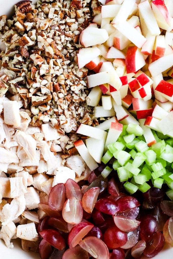 Close up image showing chopped, chicken, grapes, celery, apples and nuts before mixing.