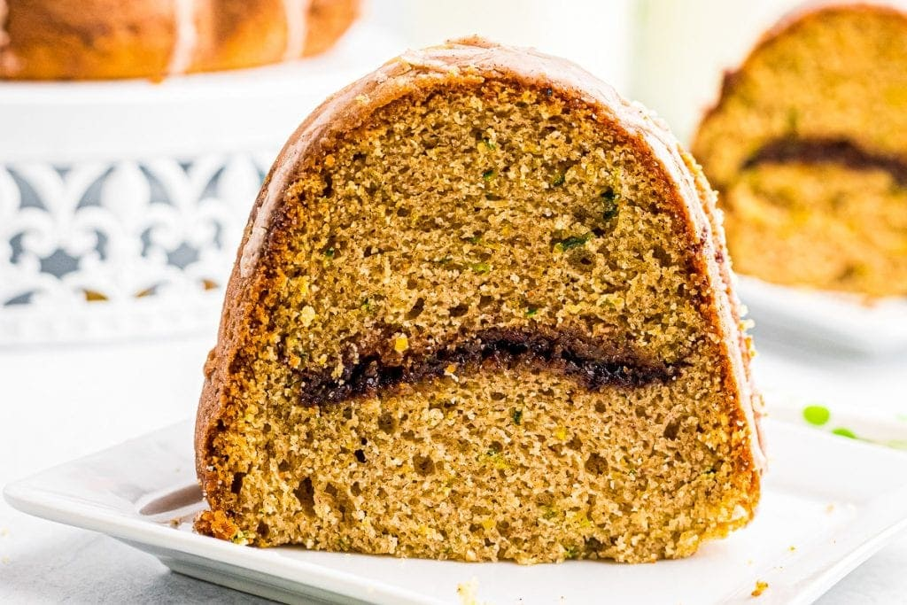 Slice of Zucchini Bundt Cake with a cinnamon layer in the middle on a white plate.