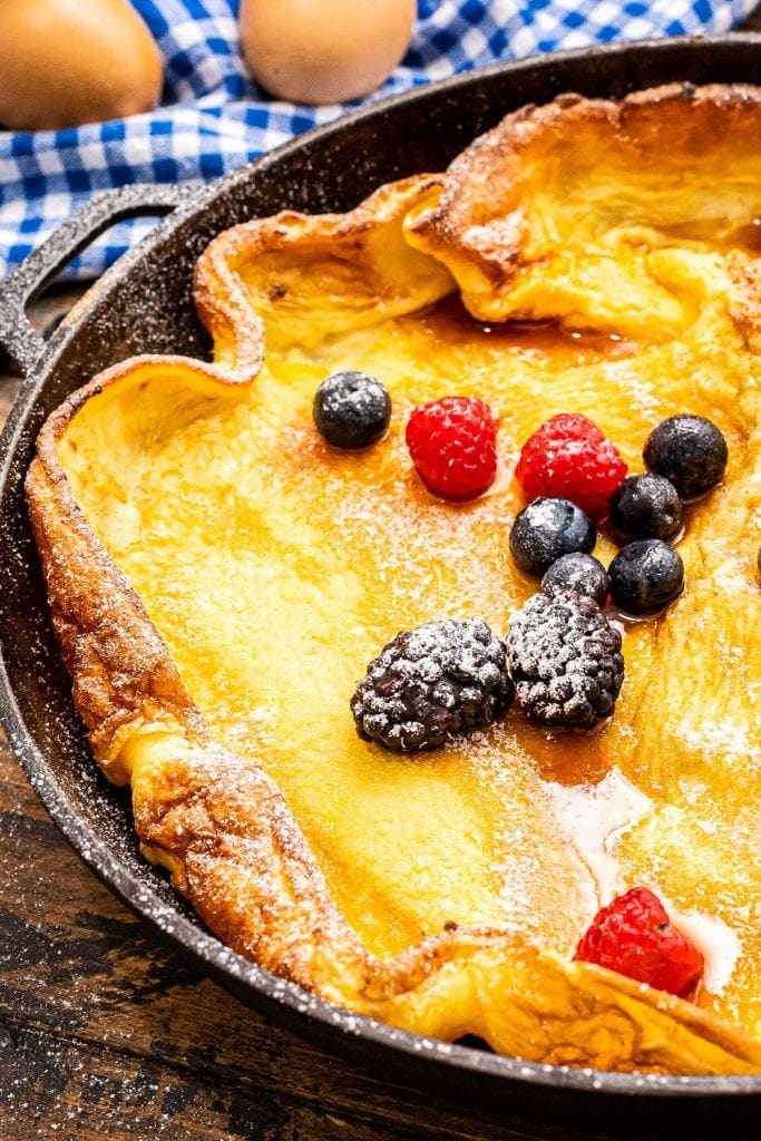 Cast Iron skillet with baked Dutch Baby Pancake topped with fresh berries in powdered sugar.