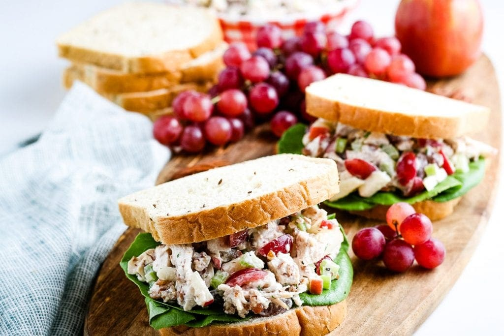 Two Chicken Salad Sandwiches on a wood cutting board with grapes and bread in background.