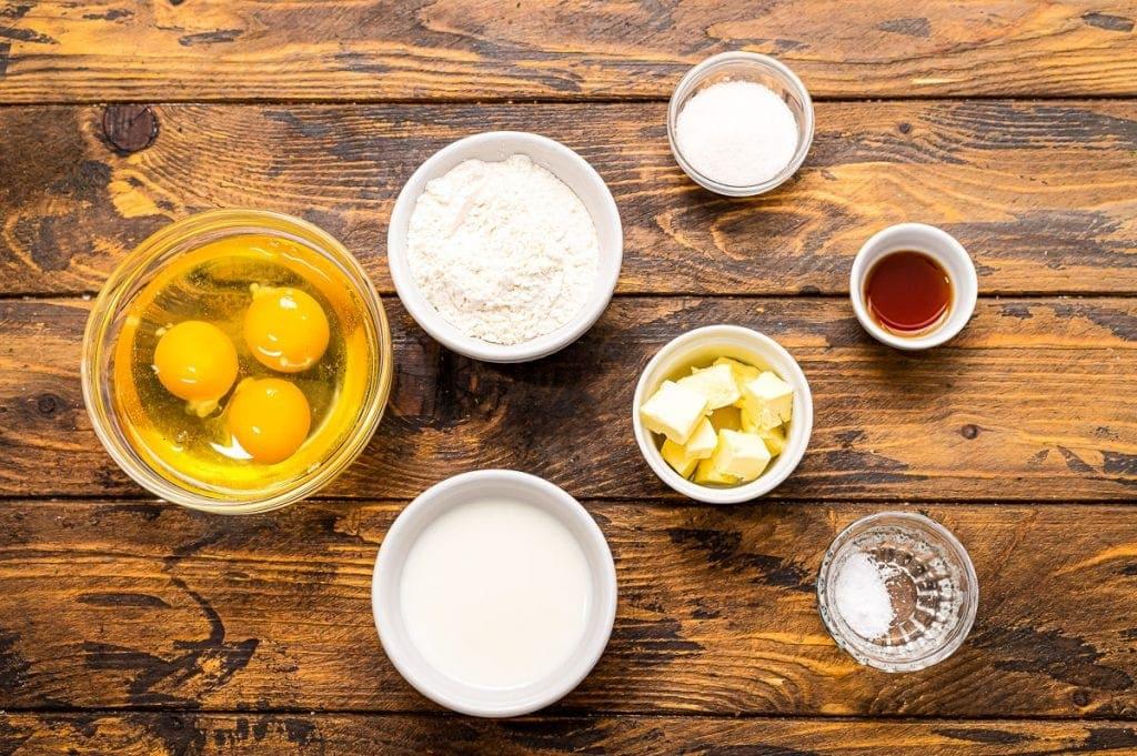 Ingredients in bowls including eggs, milk, butter, vanilla, sugar etc.
