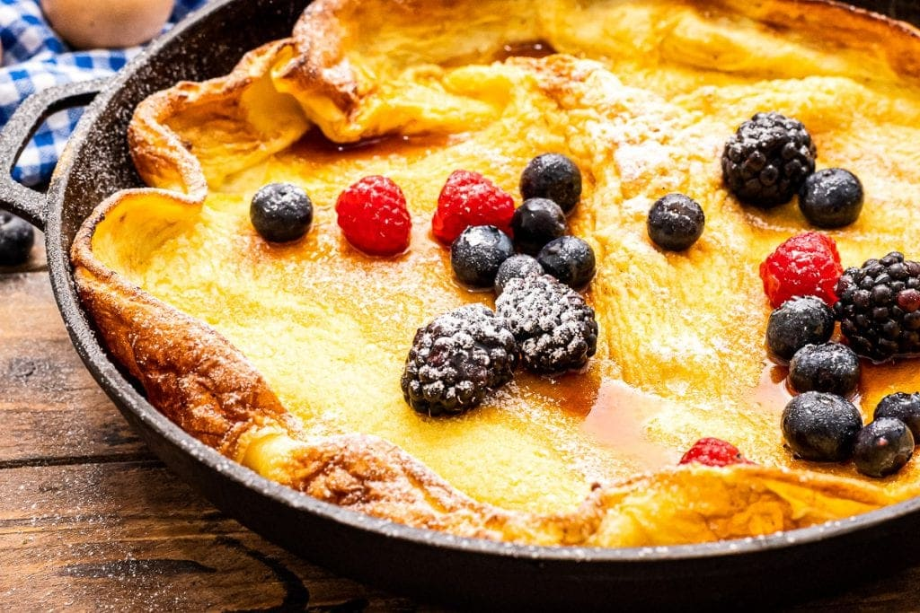 Close up image of baked Dutch Baby Pancake that's topped with berries and powdered sugar dusting.