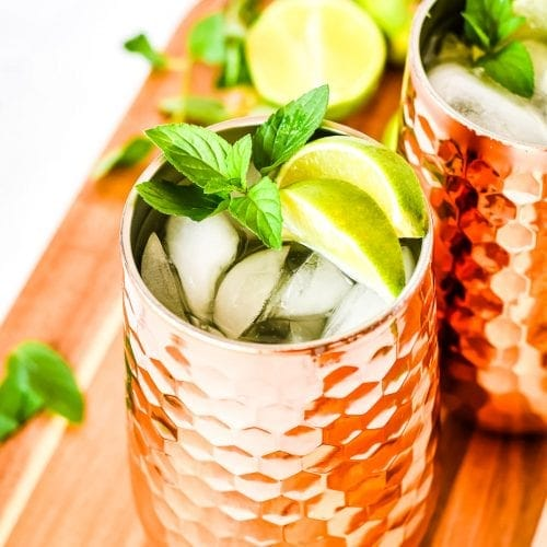 Copper mug full of ice and moscow mule garnished with lime wedges and mint on wooden cutting board.