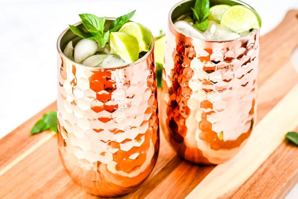 Two copper mugs with moscule mule in them garnished with lime wedges and mint on wooden board.