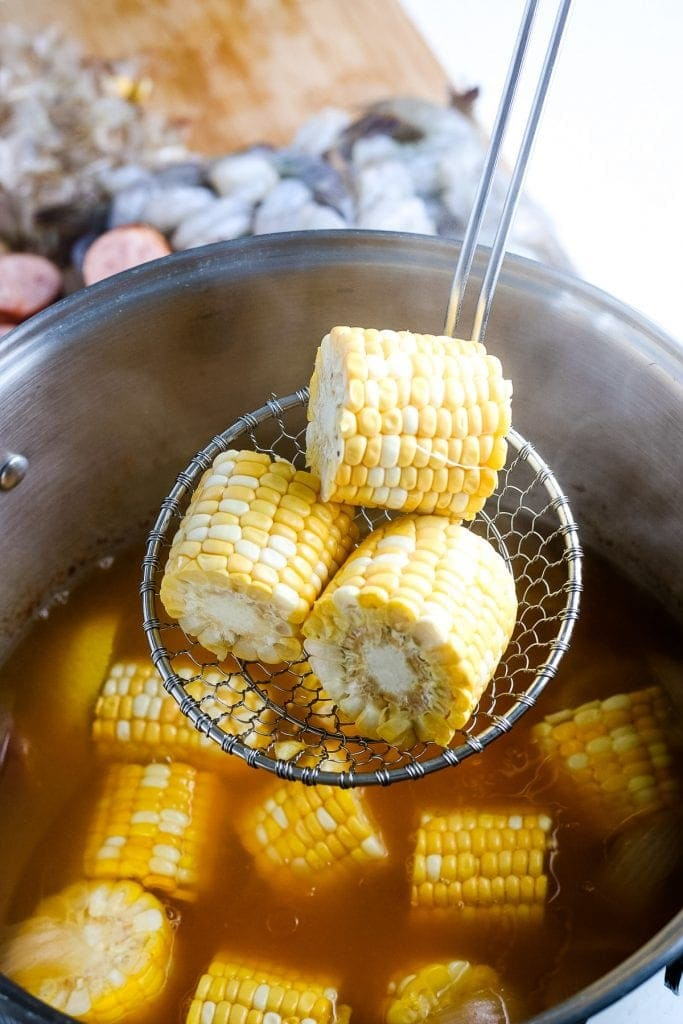 Ladle holding small pieces of corn on the cob before putting it into shrimp boil.