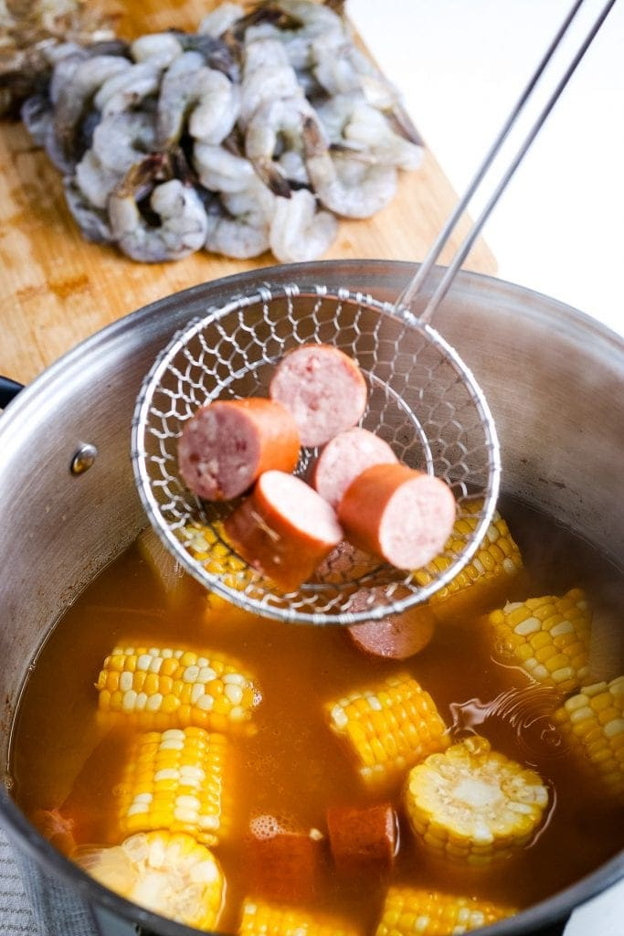 Ladle holding smoked sausage before placing it into shrimp boil pot