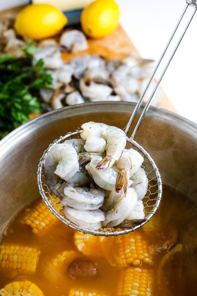Ladle placing raw shrimp into shrimp boil