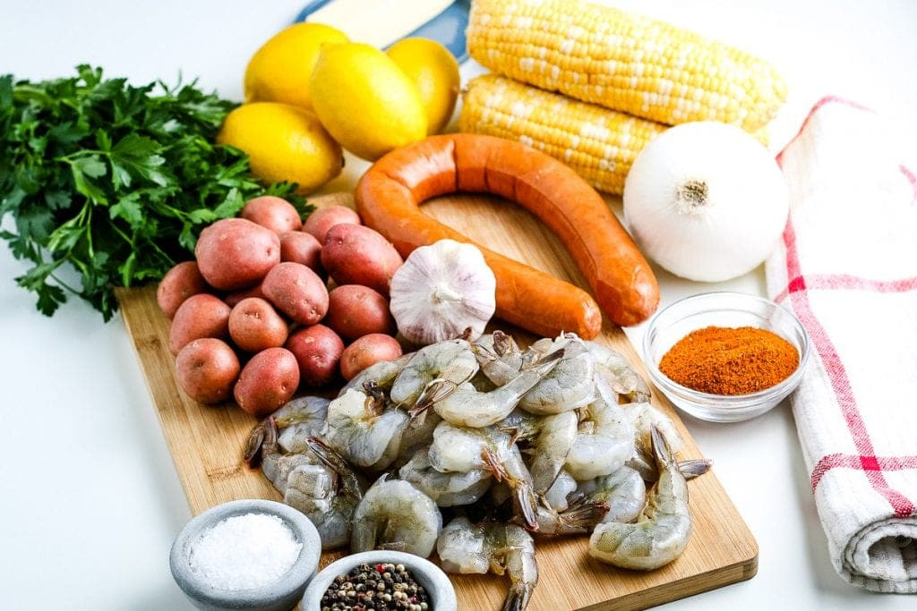 Wood cutting board showing ingredients for shrimp boil like raw shrimp, baby red potatoes, corn on the cob, smoked sausage and seaonings.