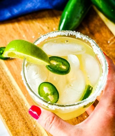 Hand holding a glass of spicy margarita that is rimmed with salt, sliced jalapenos and a lime wedge garnish