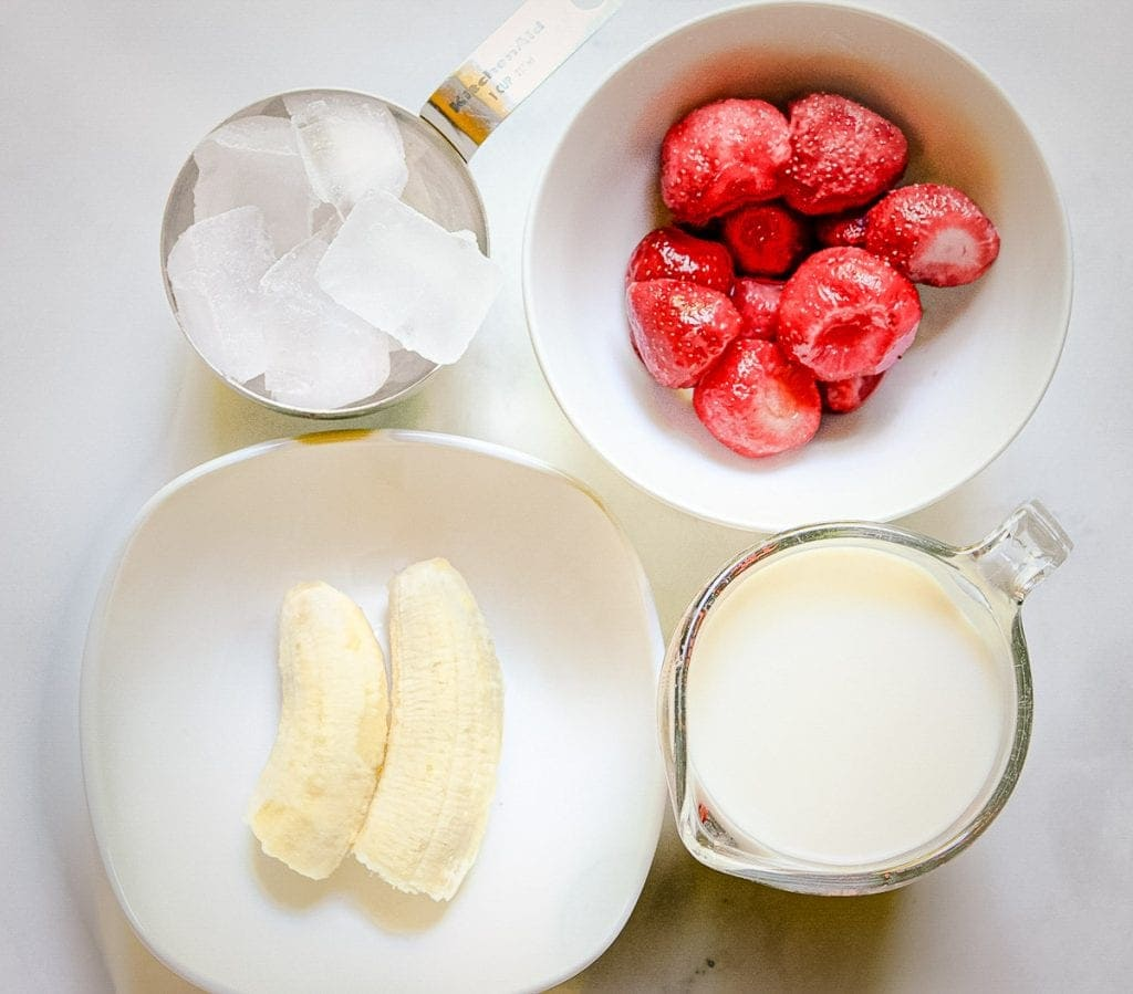 Overhead image of frozen strawberries, ice, banana and milk to make smoothie.