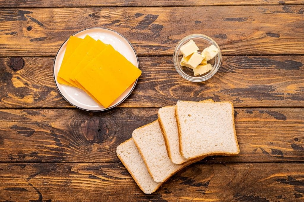 Overhead image of ingredients for recipe including cheese slices on a plate, butter in a glass dish and slices of bread.