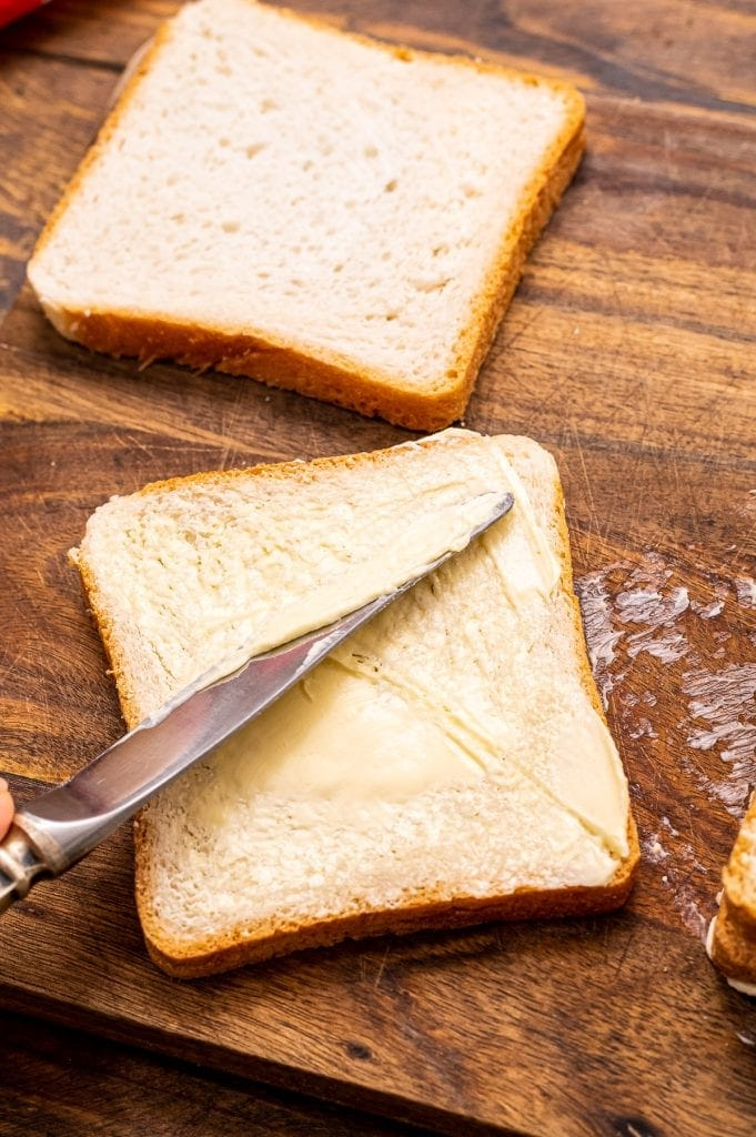 Butter knife spreading butter on a piece of bread on a wood cutting board.