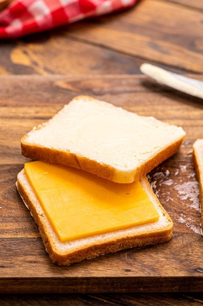 Slice of bread with a slice of cheese on top and another slice of bread half on the cheese.